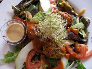 "mixed greens, alfalfa sprouts, sunflower greens, tomato, ""grilled"" onions, cucumbers, curry sauce, 3 croquettes, barbeque sauce, and house dressing"